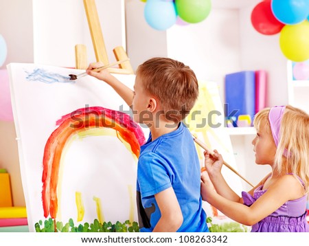 Two child painting at easel in school. Education. - stock photo