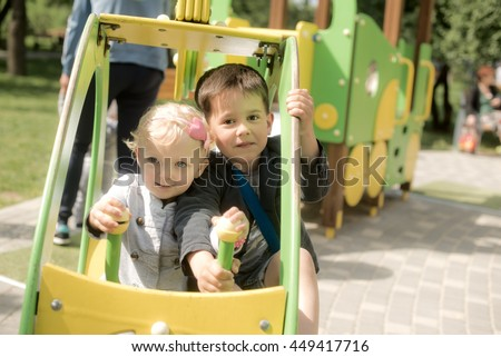 Two children, a boy and a girl playing happily together in Playground - stock photo
