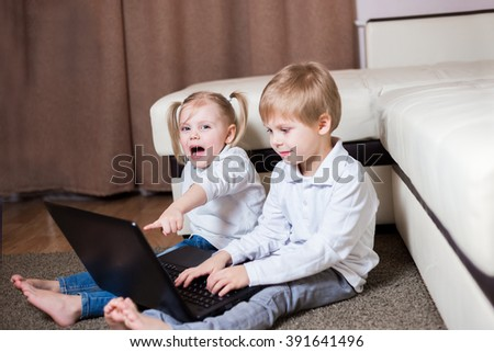 two children, a boy and girl, brother and sister sitting on the floor and shows finger in the baby monitor, looking into the camera and laughing, emotion - stock photo