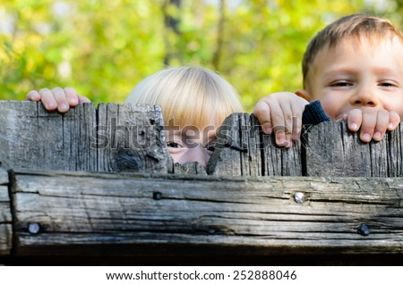 Two children, a little blond girl and boy, standing side by side peeking over an old rustic wooden fence with just their eyes visible - stock photo