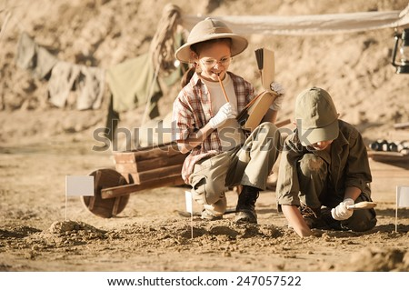 Two children archaeologists camped and conduct excavations of ancient tombs on a summer day - stock photo