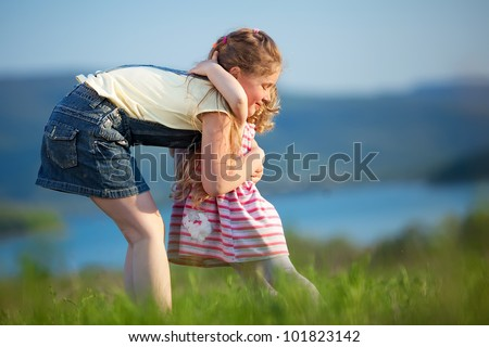 Two children are on green meadow and smile - stock photo