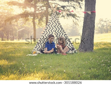 Two children are sitting in a tent teepee and holding a butterfly with a nature summertime background for an imagination or happiness concept. - stock photo