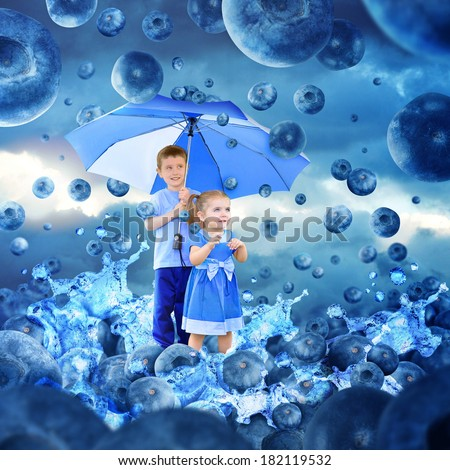 Two children are under an umbrella looking at falling blueberries for rain. Water is splashing for a fruit, diet or nutrition concept. - stock photo