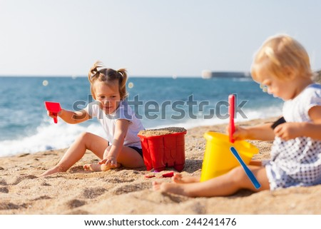 Two children at the seaside playing with sand