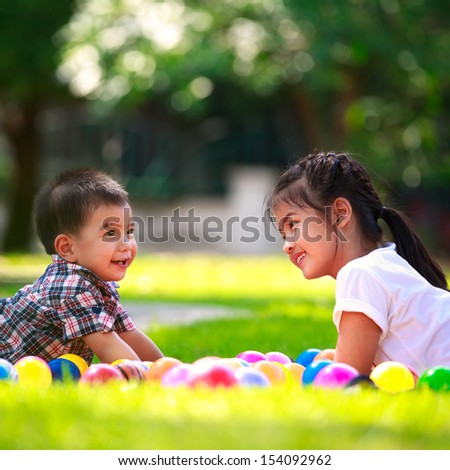 Two children, big sister and her young brother are laying on green grass and smile - stock photo