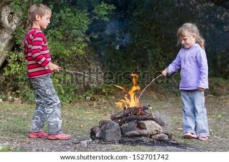 two children boy and girl playing with fire on natural background - stock photo