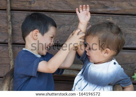 Two children boys, toddler and his older brother play fighting, concept of sibling rivalry - stock photo