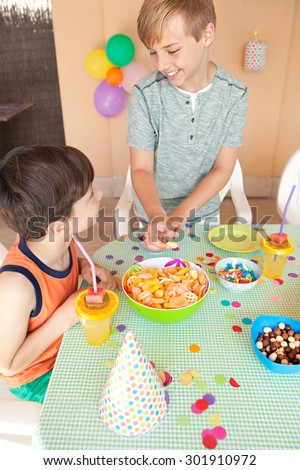 Two children brother and sister enjoying a birthday party at a celebratory fun table with food and sweets in a home garden, outdoors. Kids blowing party blowers, having fun together, home exterior.
