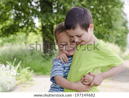 Two children brothers playing and hugging in park in nature. - stock photo