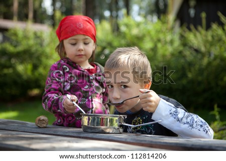 Two children camping and having a lunch outdoors. - stock photo