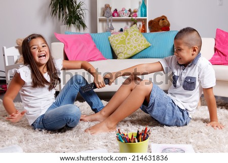 Two children fighting over the remote control - stock photo