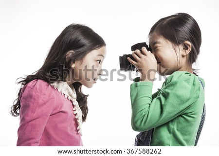 Two children girl(female, woman) hold a camera take a picture each other(together) with smile(happy) isolated white at the studio. - stock photo