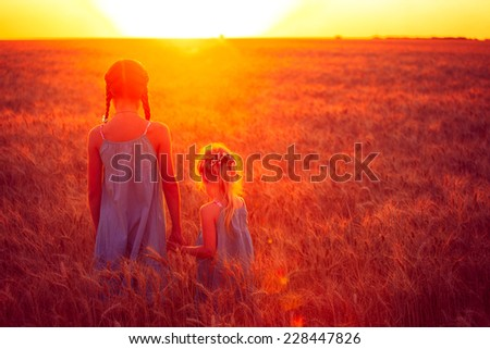 two children girls are looking at the sunset at the wheat field  - stock photo