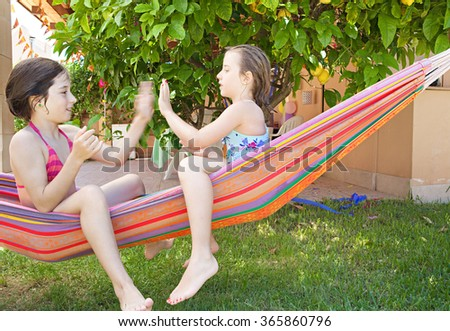 Two children girls friends playing hand clapping games together in a summer home garden holiday, relaxing sharing colorful hammock and laughing outdoors. Fun playful recreational lifestyle, vacation.