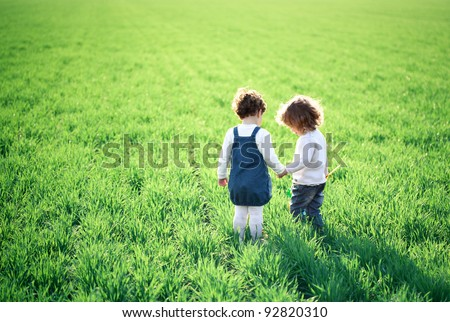 Two children going in spring green field