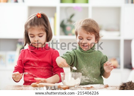 Two children having a lot of fun while cooking at home - stock photo