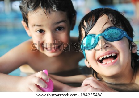 Two children having fun happy time on swimming pool - stock photo