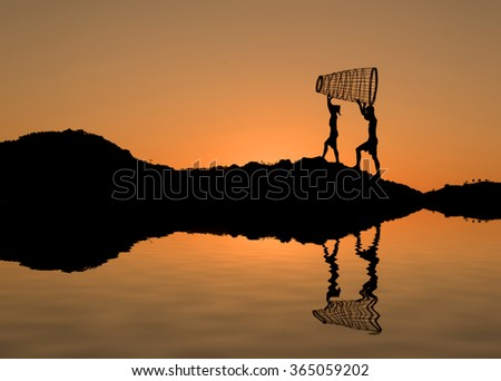 Two children help unload supplies for fish from the river . - stock photo