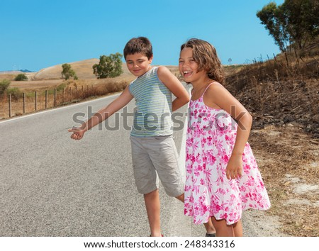 two children  hitchhiking along the street, portrait - stock photo