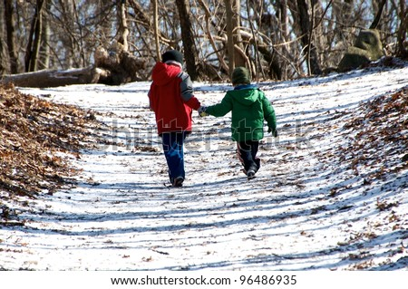 Two children hold hands and run down the path - stock photo