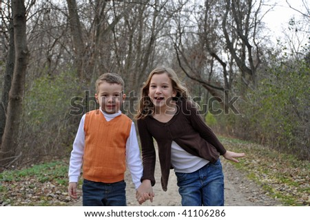 two children hold hands while on a walk in autumn - stock photo
