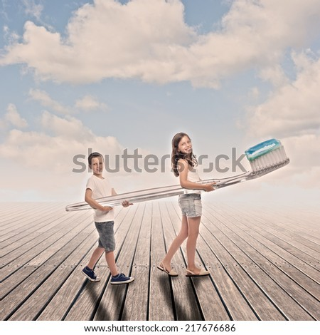 two children holding a big toothbrush on a wharf - stock photo