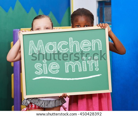 "Two children holding a chalkboard with German slogan ""Machen sie mit!"" (Join us!) - stock photo"