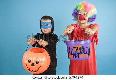 Two children holding out their Halloween containers as if ready to receive candy. - stock photo
