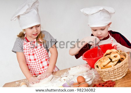 two children in chef's hats on grey background - stock photo
