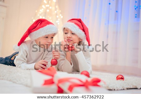 Two children in Santa hat with Christmas decorations .