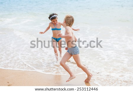 Two children in swimsuit are running on the beach - stock photo