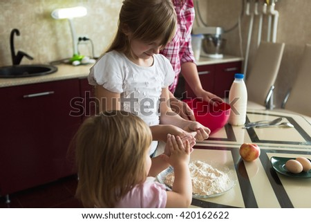 two children in the kitchen with Mom