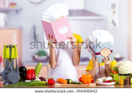 Two children in the kitchen with the food starts to cook - stock photo