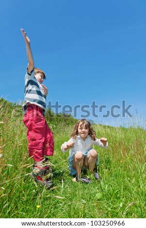 two children jumping in a meadow - stock photo