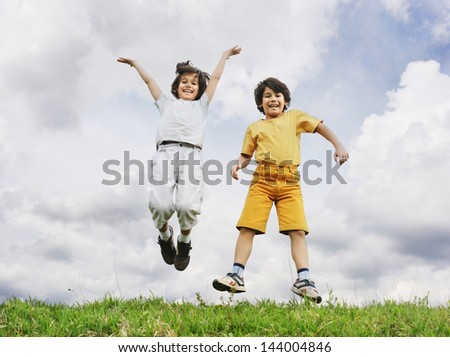 Two children jumping up on a green meadow