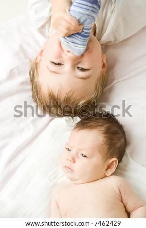 Two children laying head to head on a white sheet...one is a baby less than 6 months, the other toddler age.