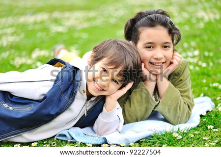 Two children laying on grass, brother and sister - stock photo