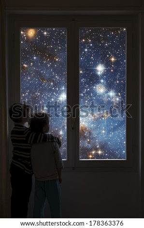 Two children look into space from a window. Elements of this image furnished by NASA. - stock photo