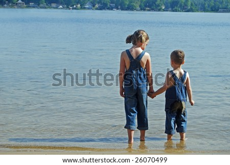 two children look out over the water while wearing their overalls - stock photo