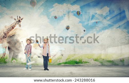 Two children of school age painting wall with roller - stock photo