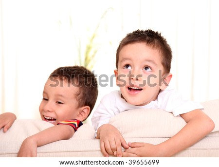 Two children on a sofa, smiling and playing - stock photo