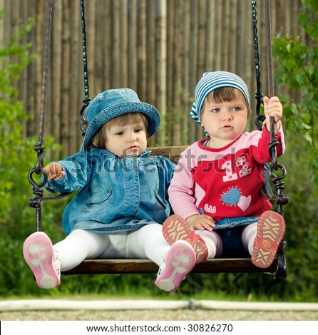 two children on the swings in park - stock photo