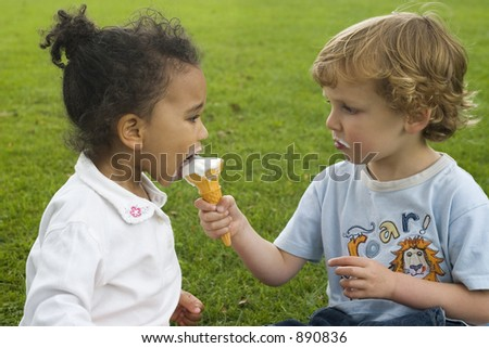 Two children, one a blond boy, one a mixed race girl sharing an ice cream