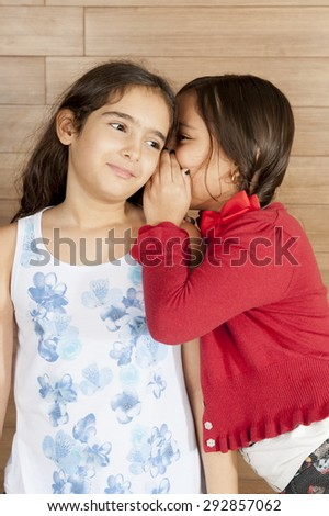Two Children, one tell a secret to the other. - stock photo