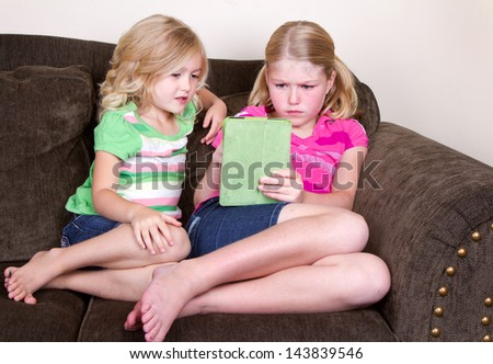 Two children or sisters using tablet, sitting on couch