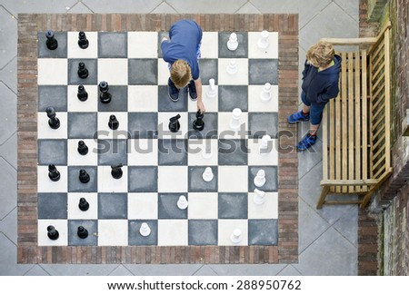 Two children playing a game of outdoor chess, seen from above - stock photo