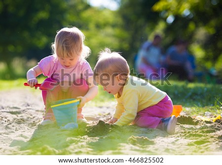 Two children playing in sandbox
