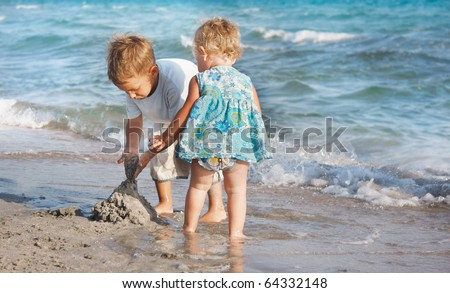 two children playing on sand beach