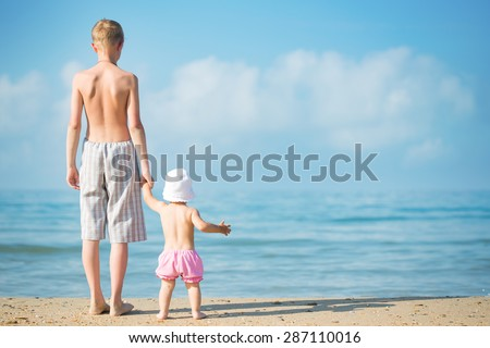 Two children playing on the beach - stock photo